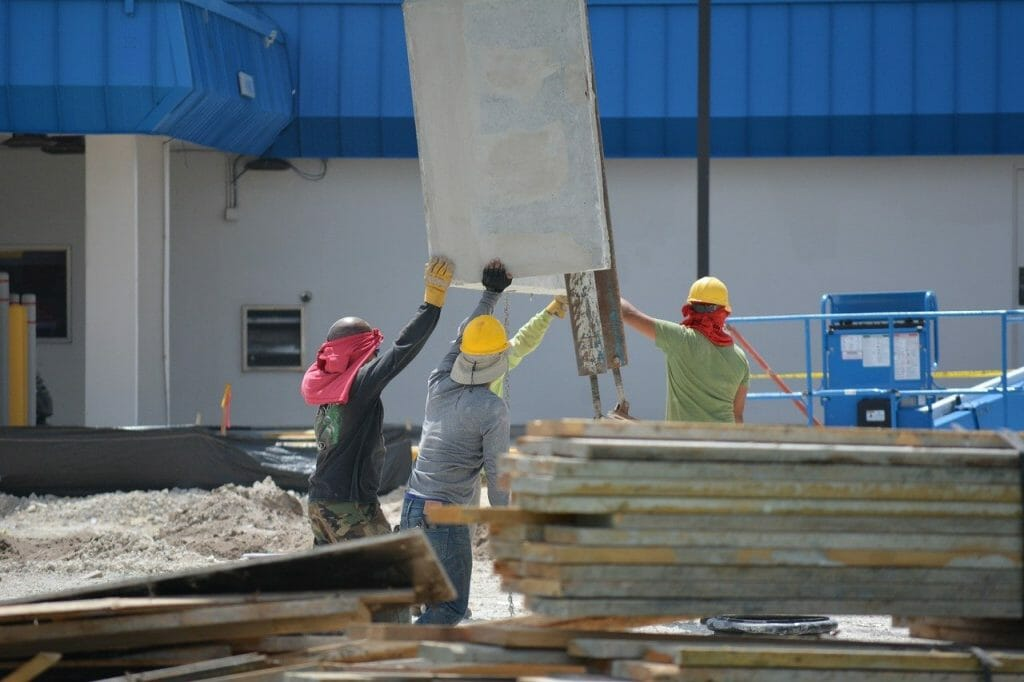 Construction workers lifting boards