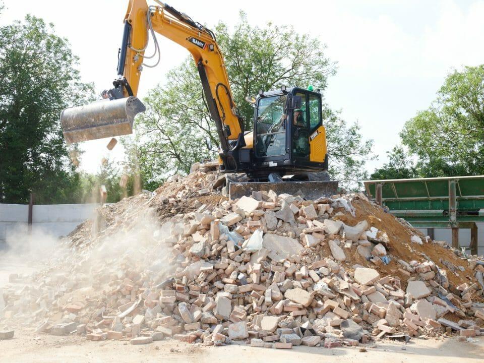Excavator load waste onto screening line